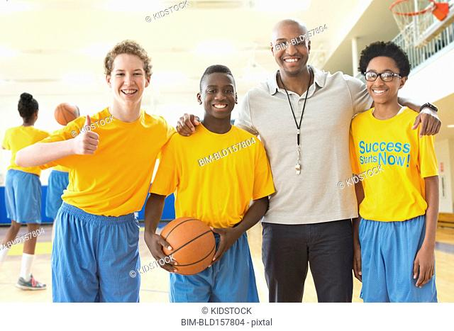 Coach smiling with basketball team in gym