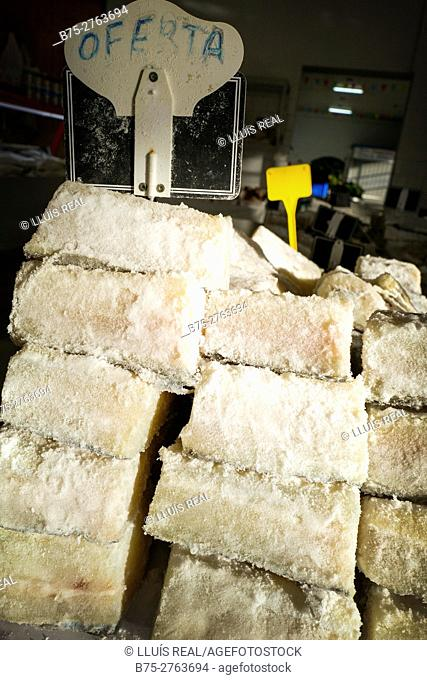"""Stacked pieces of salted cod with """"Offer"""" sign in market. Padrón, Province of La Coruña, Galicia, Spain"""