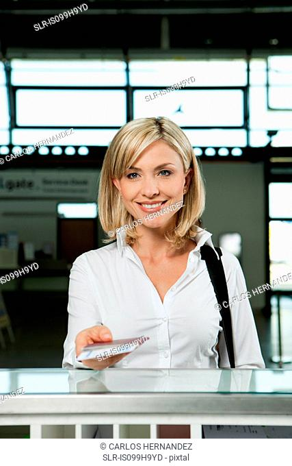 Woman with plane tickets at check in desk of airport