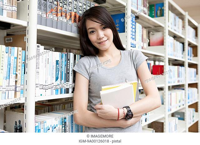 Young woman holding books in the library and looking at the camera with smile