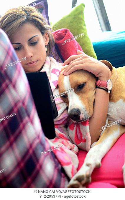 Young woman using tablet at home and hugging her dog