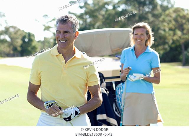Caucasian couple playing golf on course