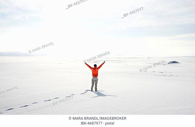 Young man stands alone in snowy landscape, snowy lava fields near Dettifoss, Norðurland eystra, Iceland