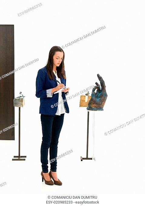 woman taking notes in an art gallery