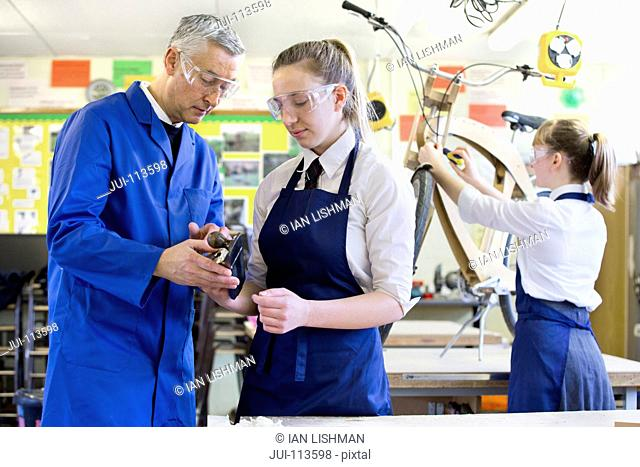 Teacher explaining tool to high school student in shop class