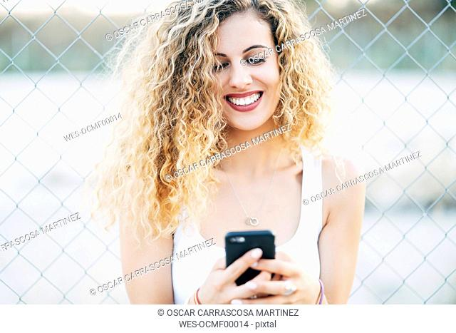 Portrait of laughing blond young woman looking at mobile phone