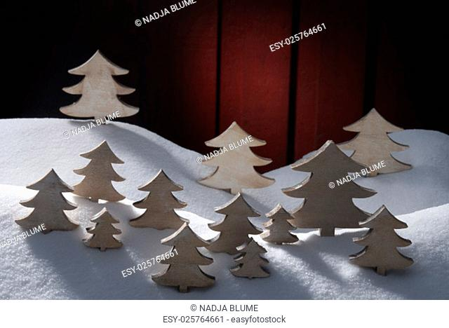 Many White Christmas Trees On Snow. White Snowy Scenery As Christmas Decoration. Christmas Time Or Advent. Red Wooden Background. Vintage, Retro Style