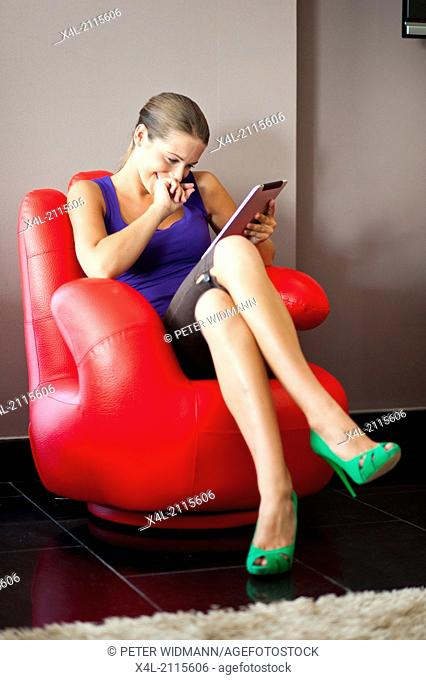young, pretty woman on summer holiday, with digital tablet, surfing the net in red finger chair (model-released)