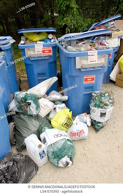 Seperate trash containers are set up in a campgroung to recycle common everyday trash