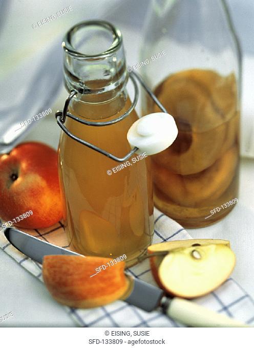 Apple Vinegar in a Glass Bottle with Fresh Apples