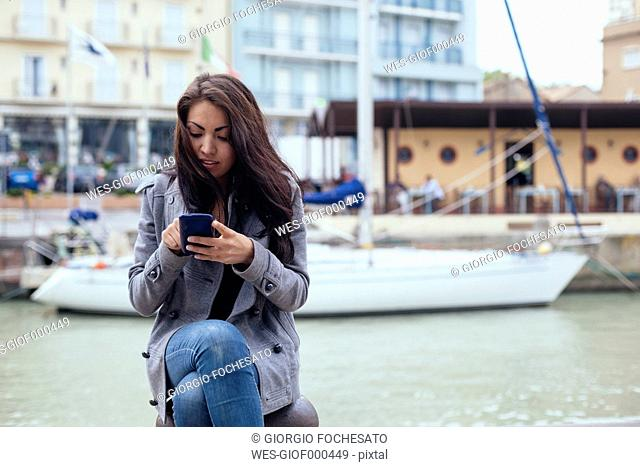 Italy, Rimini, young woman checking the cell phone at the harbor