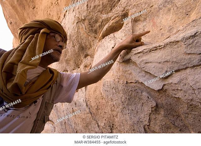 guide and prehistoric rock painting, akakus, sahara desert, fezzan, libya, africa