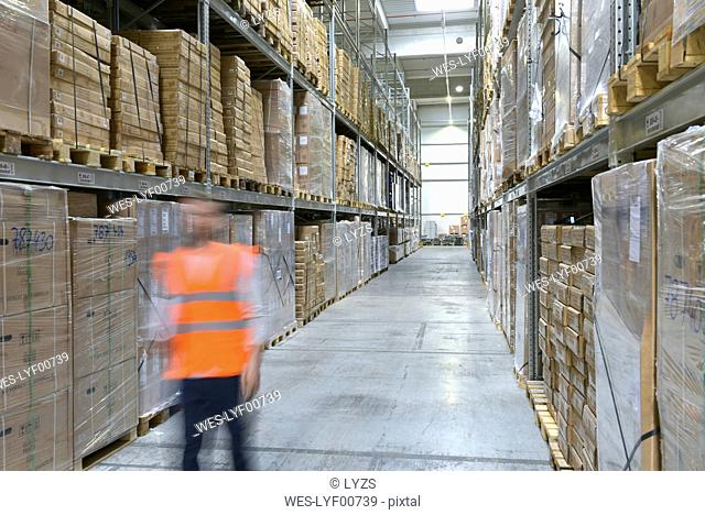 Man on the move in factory hall wearing safety
