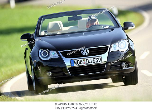 VW Volkswagen Eos 2.0 TFSI, model year 2006-, black, driving, diagonal from the front, frontal view, country road, open top