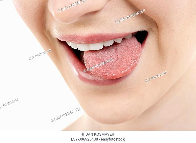 Close-up image of a teasing woman with tongue out against the white background