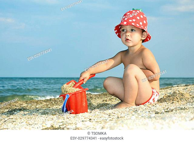 Little girl in summer on the sea makes a house of sand, bright sunny day