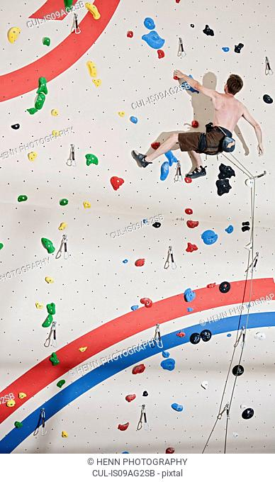 Mid adult man climbing with ropes on climbing wall