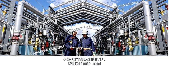 MODEL RELEASED. Oil refinery workers and pipework