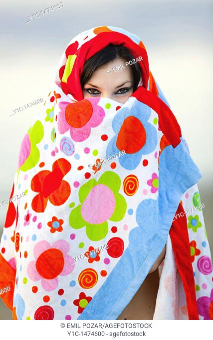 Attractive young woman enveloped with a colorful towel