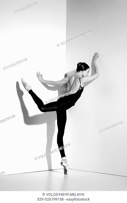 Ballerina in black outfit posing on pointe shoes, studio gray background