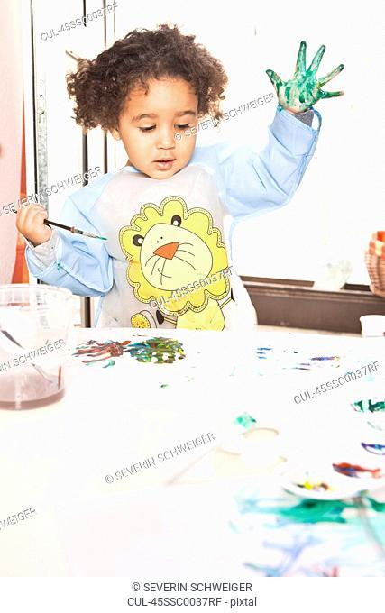 Girl finger painting on paper