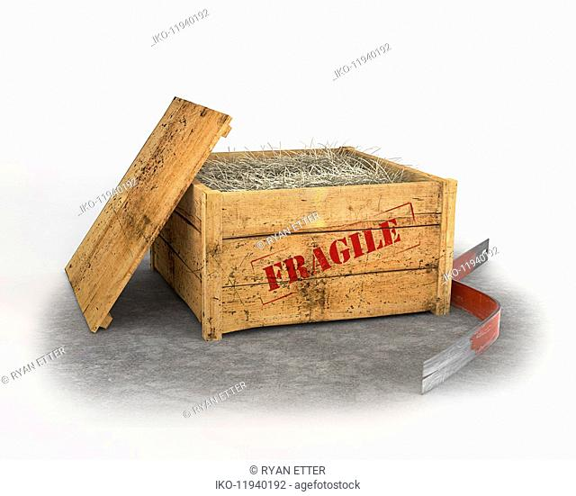 Open wooden crate with straw inside and fragile stamp