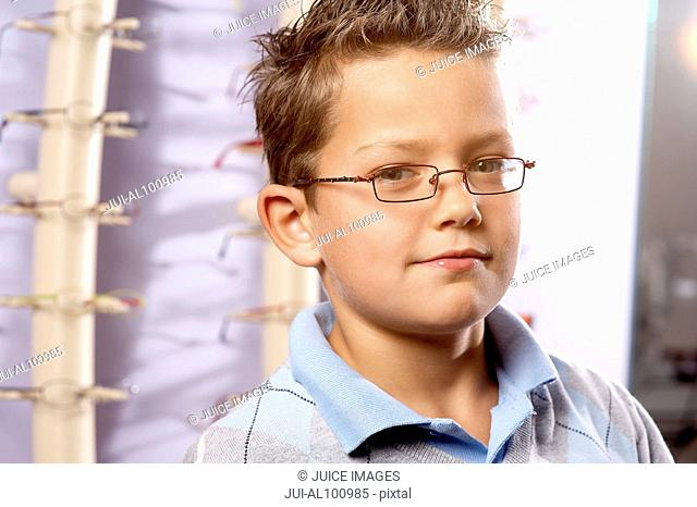 Boy trying on eyeglasses in optician's office