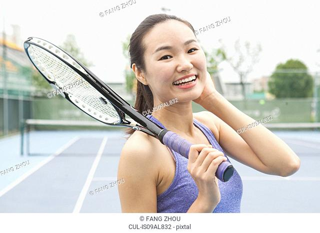 Portrait of young female tennis player on tennis court