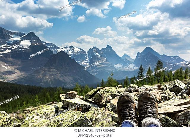 Hiker's boots resting on a rocks with valley and mountain range in the background; British Columbia, Canada