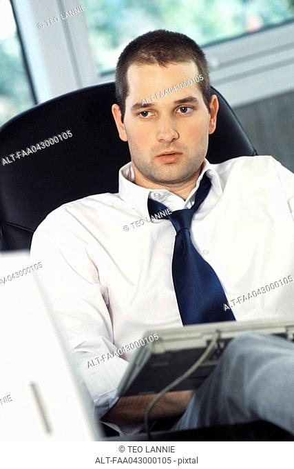 Man with feet up on office desk, typing on computer keyboard set on lap