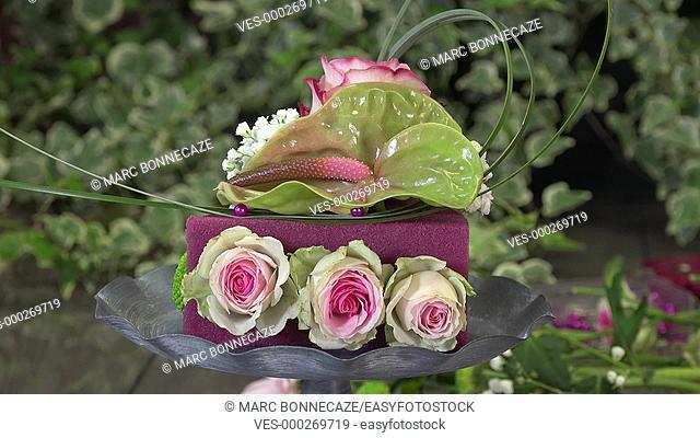 creating a flower arrangement shaped as a cake