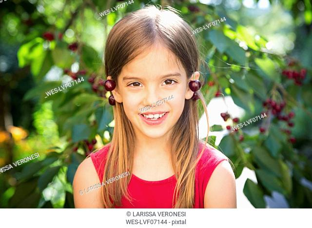 Little girl with cherries on ears