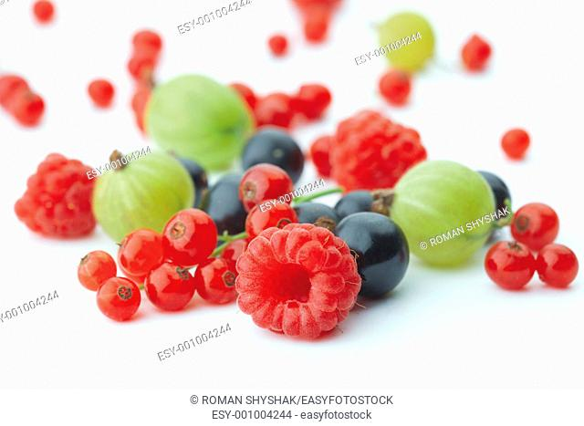 Spilled mixed berries on white background whith a raspberry in the foreground in focus