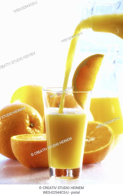 Orange juice been poured into glass