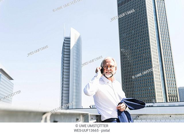Confident mature businessman in the city on cell phone