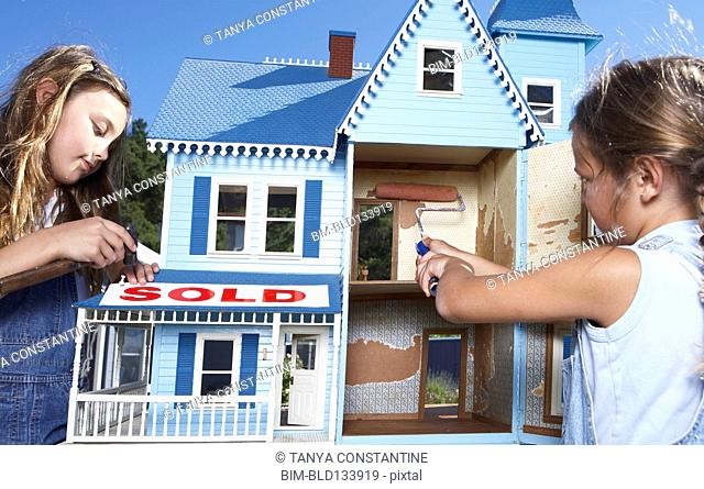 Mixed race girls fixing up doll house for sale