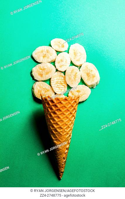 Still life parody on fresh fruit ice-cream cone on aqua green background. Bananas over sorbet