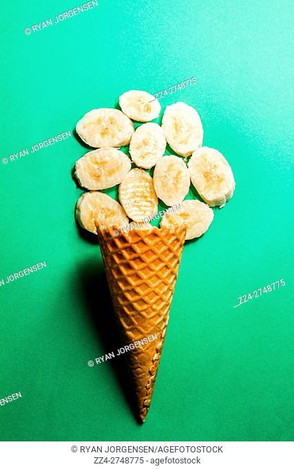 Still life parody on fresh fruit ice-cream cone on aqua green background. Bananas over sorbet