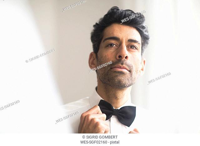 Portrait of man adjusting his bow tie