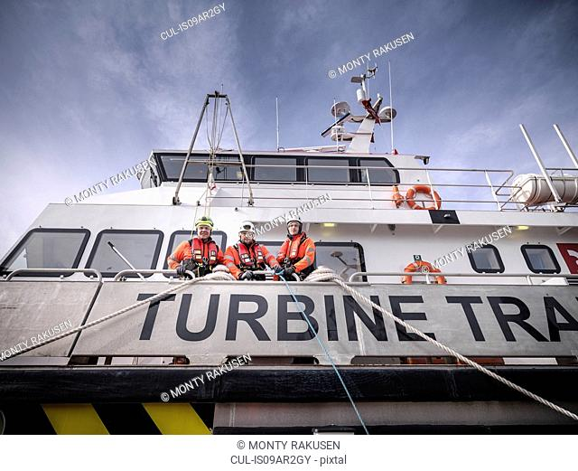 Portrait of offshore windfarm engineers in port on ship