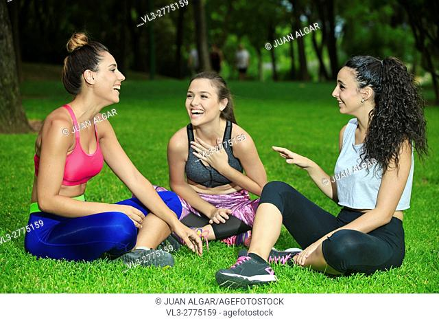 Leg crossed laughing friends having fun after training in park