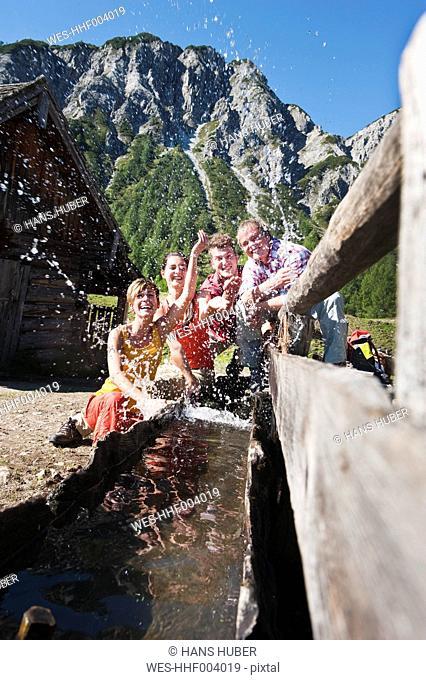 Austria, Salzburg County, Men and women splashing water at water trough near alpine hut