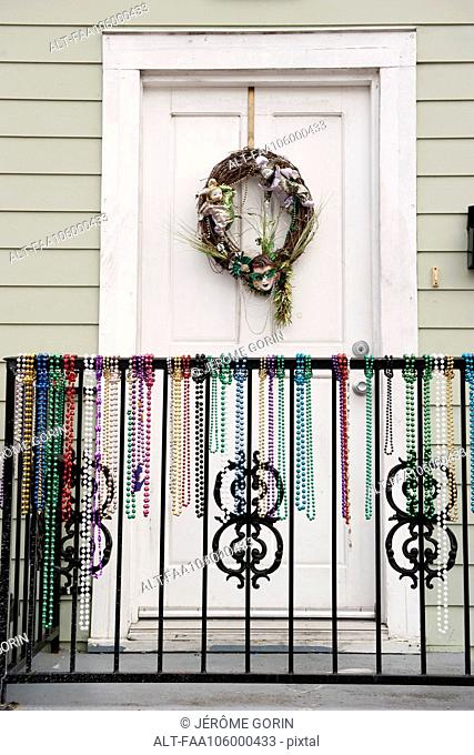 Festive wreath and mardi gras beads on entrance to home