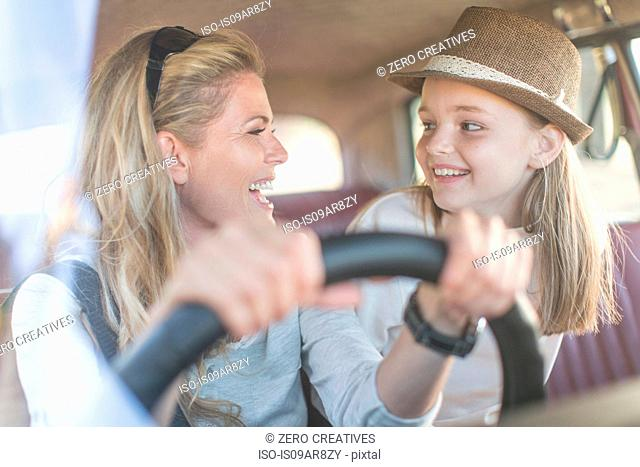 Mother and daughter in car together, smiling