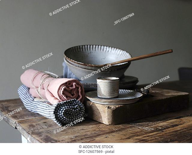 Bakery shapes near dishcloths, paddle, plates and bowls on wooden table on grey background
