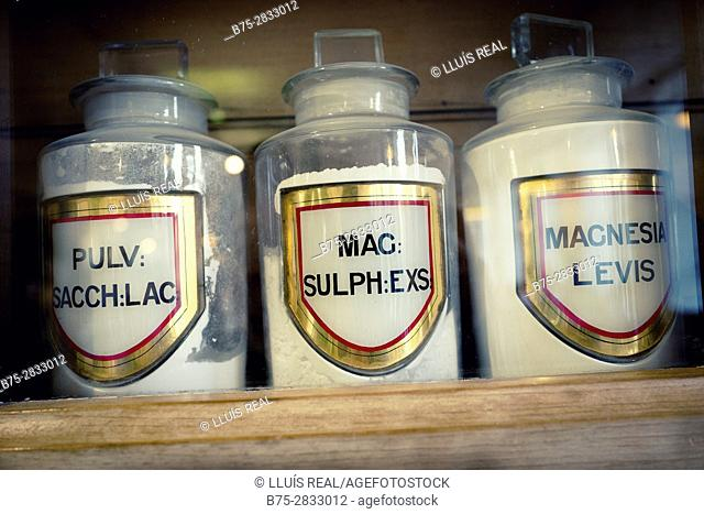 "Close-up of three vintage pharmacy jars reading: ""PULV: SACCH:AC"", ""MAG: SULPH:EXS"",  ""MAGNESIA LEVIS"". Saltaire Bradford, West Yorkshire, UK"