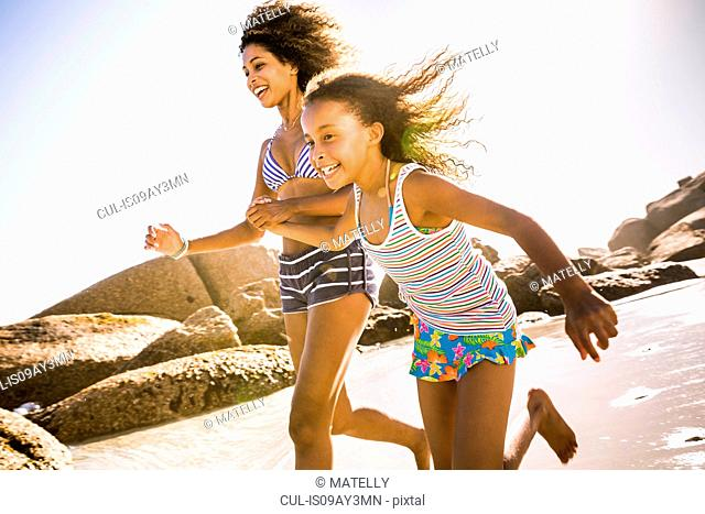 Girl and mother running on beach, Cape Town, South Africa