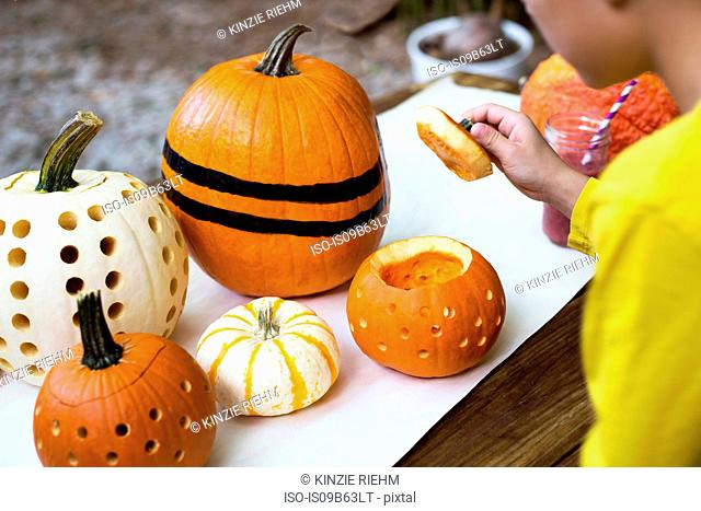 Over shoulder view of boy lifting pumpkin lid on garden table