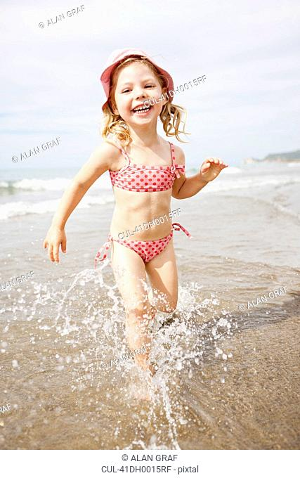 Smiling girl playing in waves on beach