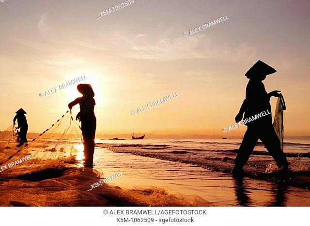 Three women in traditional hats on Mui Ne Beach, Vietnam  Fishing at sunrise